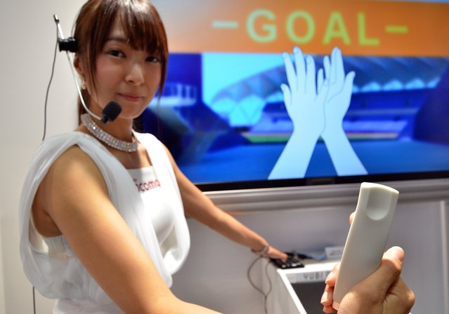 """A model displays Japanese mobile communication giant NTT Docomo's mobile navigation device """"Yubi Navi"""" (Finger Navigator) which uses tactile sensations to guide the user at the CEATEC electronics trade show in Chiba, suburban Tokyo on October 7, 2014. Some 550 companies and organization exhibit their latest products and technology through October 11. (Photo by Yoshikazu Tsuno/AFP Photo)"""