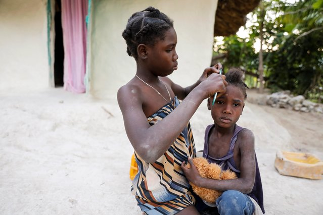 Two girls, daughters of Celavi Belor, spend time together outside their house in Jean-Rabel, Haiti on January 31, 2020. (Photo by Valerie Baeriswyl/Reuters)
