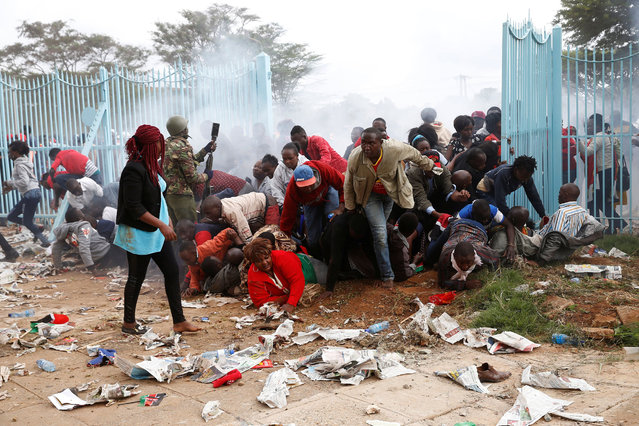 People fall as police fire tear gas to try control a crowd trying to force their way into a stadium to attend the inauguration of President Uhuru Kenyatta at Kasarani Stadium in Nairobi, Kenya November 28, 2017. (Photo by Baz Ratner/Reuters)