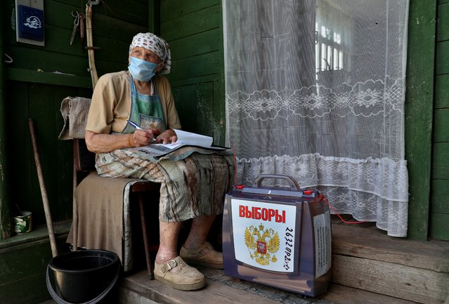 A local resident fills in documents near a mobile ballot box outside her house during a seven-day vote on constitutional reforms, in the village of Troitskoye in Moscow region, Russia on June 25, 2020. (Photo by Evgenia Novozhenina/Reuters)