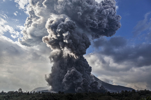 Mount Sinabung spews pyroclastic smoke, seen from Tiga Pancur village on October 13, 2014 in Berastagi, Karo district, North Sumatra, Indonesia. Mount Sinabung, which has lain dormant for over 400 years, has been intermittently erupting since September 15 last year, killing 15 people and forcing hundreds to flee their homes. According to The National Disaster Mitigation Agency, more than 3,000 residents are still displaced. (Photo by Ulet Ifansasti/Getty Images)