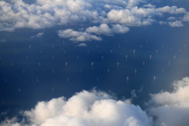 Burbo Bank Offshore Wind Farm on the Burbo Flats in Liverpool Bay, operated by DONG Energy, is pictured from the the window of an aircraft flying over the Irish Sea, off the west coast of northern England, on November 8, 2017. British energy supplier SSE and German-owned Npower said Wednesday they have agreed to merge their businesses that heat and light up millions of UK households. SSE, the second largest energy supplier in Britain, said it would spin off its household energy and services business and combine it with Npower, the British arm of Germany's Innogy. (Photo by Paul Ellis/AFP Photo)