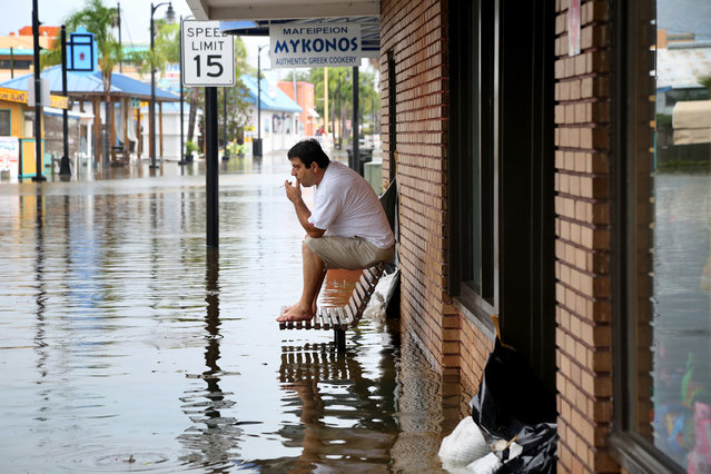 Pedro Muacaj rests on higher ground in front of a gift shop along a flooded section of  Dodecanese Blvd. in Tarpon Springs, Fla. where he was working. Thursday, September 1, 2016. The street, which typically floods during heavy reins, was filling quickly at high tide as Tropical Storm Hermine strengthened in the Gulf of Mexico, (Photo by Douglas R. Clifford/The Tampa Bay Times via AP Photo)