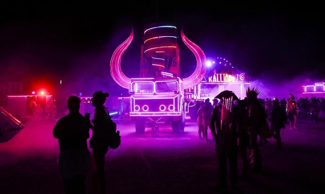 In this Tuesday, August 30, 2016 photo, attendees walk by art cars during Burning Man at the Black Rock Desert near Gerlach, Nev. (Photo by Chase Stevens/Las Vegas Review-Journal via AP Photo)