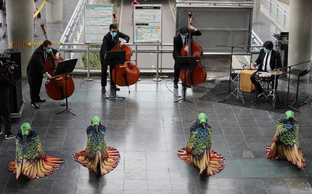 "Musicians from Bogota's Youth Philharmonic Orchestra and dancers in hummingbird costumes perform for commuters at a bus stop in Bogota, Colombia, Friday, July 24, 2020. They offered a one-hour concert that they say they hope will serve as a ""therapy"" to cope with the new coronavirus pandemic. (Photo by Fernando Vergara/AP Photo)"