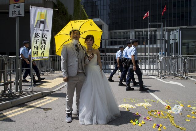 A Hong Kong couple holding a yellow umbrella, the symbol of the Occupy Central movement, poses during a pre-wedding photoshoot in front of the government headquarters, as policemen walking past, in Hong Kong, China September 28, 2015. Monday marks the first anniversary of the movement. (Photo by Tyrone Siu/Reuters)