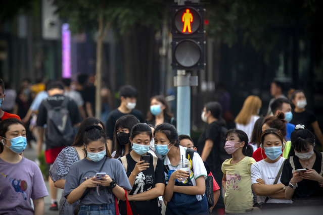 People wearing face masks to protect against the coronavirus wait to cross an intersection in Beijing, Wednesday, July 29, 2020. China reported more than 100 new cases of COVID-19 on Wednesday as the country continues to battle the outbreak in Xinjiang. (Photo by Mark Schiefelbein/AP Photo)