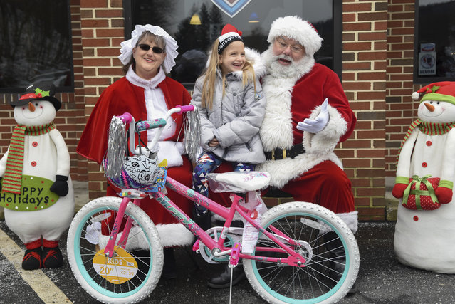 Alexa Paulukonis, 7, of West Hazleton, Pa., sits with  a couple dressed as Santa Claus and Mrs. Claus after receiving her bicycle during the bike giveaway at Red White and Blue Autos, Inc. in Ashland, Pa., on Sunday, December 17, 2017. The dealership was giving away new bicycles to local children for Christmas. (Photo by Jacqueline Dormer/The Republican-Herald via AP Photo)