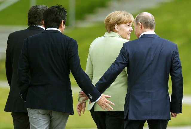 Japan's Prime Minister Shinzo Abe (2nd L) touches hands with Russia's President Vladimir Putin as they walk with Germany's Chancellor Angela Merkel, after a G8 summit group photograph was taken at the Lough Erne golf resort in Enniskillen, Northern Ireland June 18, 2013. (Photo by Andrew Winning/Reuters)
