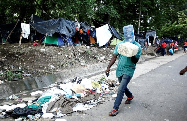 An African migrant stranded in Costa Rica walks to collect water on the Inter-American Highway at the border between Costa Rica and Nicaragua, in Penas Blancas, Costa Rica, September 8, 2016. (Photo by Juan Carlos Ulate/Reuters)