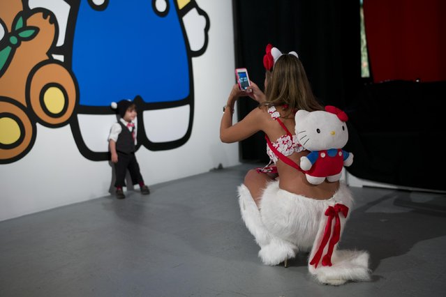 Jessica Aguilar takes pictures of her nephew at the Hello Kitty Con, the first ever Hello Kitty fan convention, held at the Geffen Contemporary at MOCA Thursday, October 30, 2014, in Los Angeles. (Photo by Jae C. Hong/AP Photo)