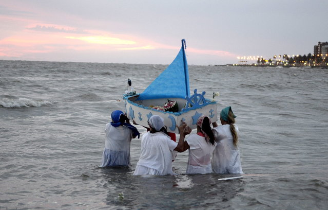 Faithful carry a boat out to sea, filled with offerings to Yemanja, the African sea goddess, during a ceremony honoring the deity in Montevideo, Uruguay, Saturday, February 2, 2013. Thousands of worshippers come to the beach in Montevideo on her feast day, February 2, bearing candles, flowers, perfumes and fruit to show their gratitude for her blessings bestowed upon them. The belief in the goddess sprouts from Umbanda, a blend of religions that include African, Catholicism and Spiritism. (Photo by Matilde Campodonico/AP Photo)