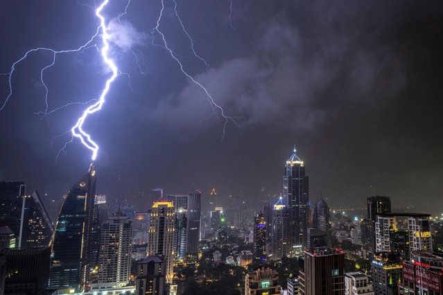 In this picture taken on October 27, 2019 lightening strikes on a building during a thunderstorm in Bangkok. (Photo by Mladen Antonov/AFP Photo)