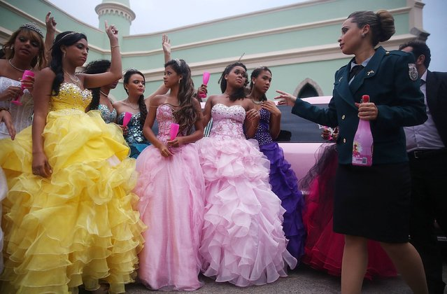 "Teenage girls from the Cerro-Cora ""favela"", or community, arrive with a UPP officer (R) at a group debutante ball at Ilha Fiscal castle organized by the Pacifying Police Unit (UPP) from their community on November 6, 2014 in Rio de Janeiro, Brazil. The gala was held in the castle on Guanabara Bay and relied on volunteers who prepared makeup, hair dressing and loaned dresses, in an effort to build goodwill between ""favela"" residents and the community's police force. (Photo by Mario Tama/Getty Images)"