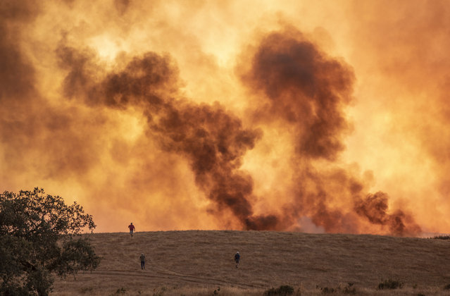 Smoke billows from a wildfire near the town of Almonaster la Real in Huelva, Spain on August 30, 2020. At least 3,200 people were evacuated because of a fire that has already ravaged some 10,000 hectares in the southwestern Spanish province of Huelva and which remains active, according to local authorities. (Photo by A. Perez/AP Photo)