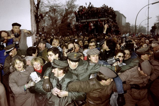 East and West German police contain the crowd of East Berliners flowing through the recent opening made in the Berlin Wall at Potsdamer Square on November 12, 1989. (Photo by Patrick Hertzog/AFP Photo)