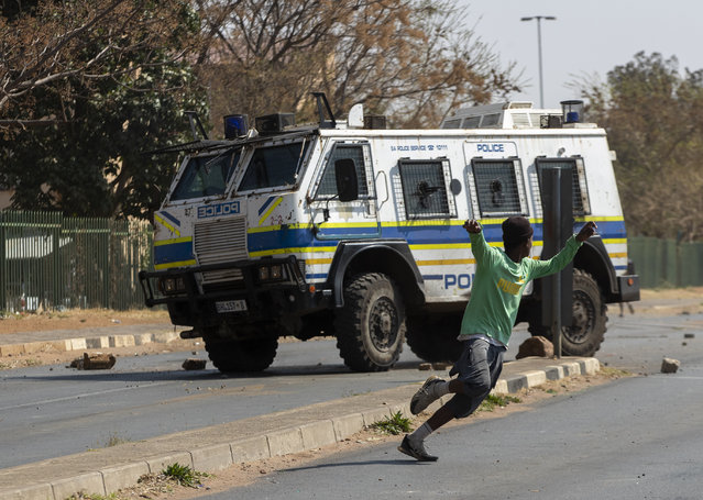Protesters run for cover as they clash with police in Eldorado Park, Johannesburg, South Africa, Thursday, August 27, 2020. Residents from the township, south of Johannesburg are demanding justice for a teenager shot and killed, allegedly at the hands of police Wednesday. (Photo by Themba Hadebe/AP Photo)