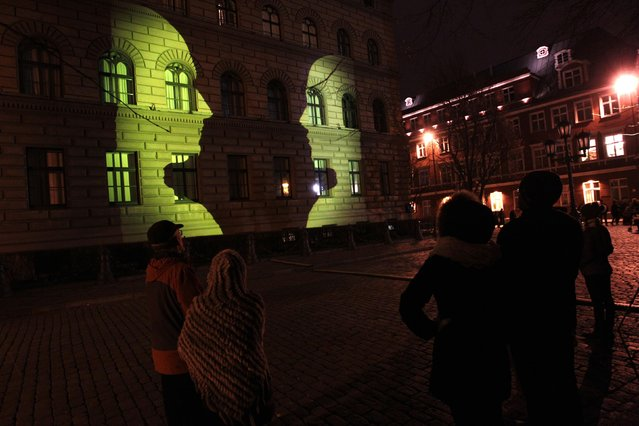 "People watch a light performance on the walls of the Latvian Parliament House during the ""Staro Riga"" festival of lights in Riga November 15, 2014. (Photo by Ints Kalnins/Reuters)"