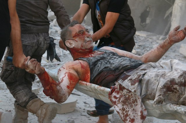 A wounded man is being carried as search and rescue team members evacuate casualties from the rubbles after the Syrian regime forces airstrikes hit Aleppo's opposition controlled Al-Ansari town, Syria on September 22, 2016. (Photo by Ibrahim Ebu Leys/Anadolu Agency/Getty Images)