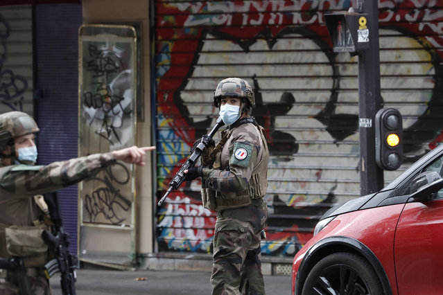 """French soldiers patrol after four people have been wounded in a knife attack near the former offices of satirical newspaper Charlie Hebdo, Friday September 25, 2020 in Paris. A police official said officers are """"actively hunting"""" for the perpetrators and have cordoned off the area including the former Charlie Hebdo offices after a suspect package was noticed nearby. Islamic extremists attacked the offices in 2015, killing 12 people. (Photo by Thibault Camus/AP Photo)"""