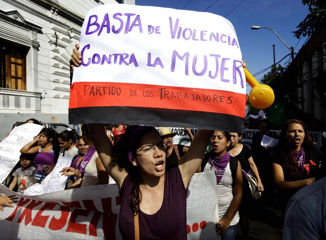 "Women shout slogans as they protest violence against women during a march in Asuncion, Paraguay. The poster reads in Spanish ""Enough violence against women"". (Photo by Jorge Saenz/Associated Press)"