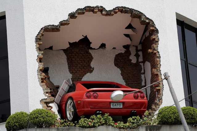Part of a Ferrari car is seen inside the exterior wall of a tyre and wheels business in Sao Paulo, Brazil, October 16, 2015. The Ferrari was installed by the business owner. Shares in Fiat Chrysler Automobiles (FCA) fell more than 3 percent in early trade on Wednesday, after the flotation of its luxury unit Ferrari was priced at the top end of the range but below the expectations of some investors. (Photo by Nacho Doce/Reuters)