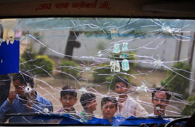Indian civilians look at a school bus riddled with bullet marks, allegedly from firing from the Pakistan side of the border, at a residential area near the international border at Mawa village, in Samba district, about 58 kilometers south of Jammu, India, Saturday, October 24, 2015. India on Friday accused Pakistan of a cease-fire violation in Kashmir in which one Indian civilian was killed and another was wounded. (Photo by Channi Anand/AP Photo)
