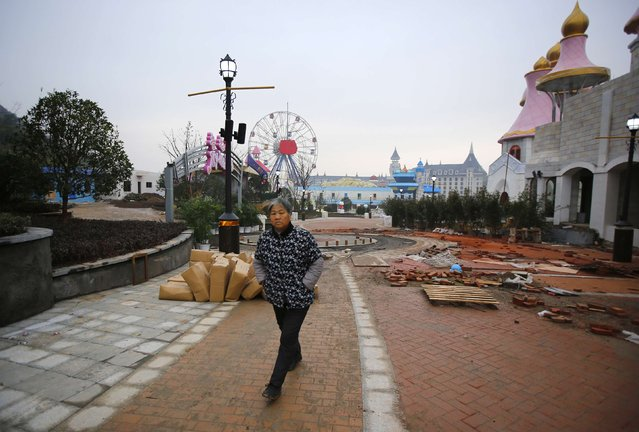 A local resident walks at a section of a Hello Kitty amusement park undergoing construction in Anji, Zhejiang province November 28, 2014. (Photo by Carlos Barria/Reuters)