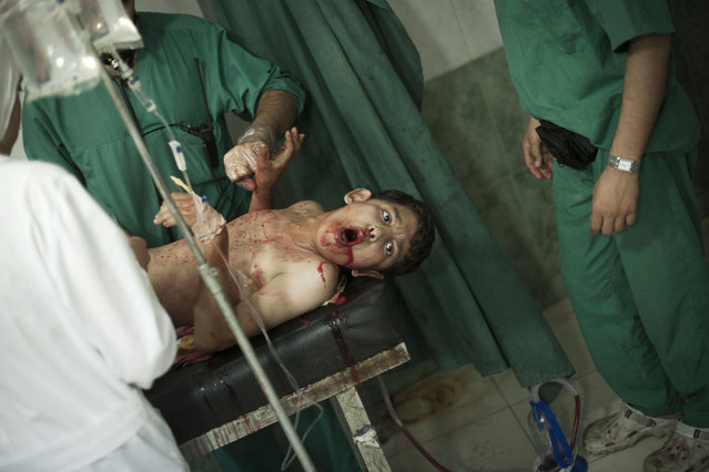 Syrian doctors try to save the life of a boy, shot by a Syrian Army sniper, at Dar El Shifa hospital in Aleppo, Syria, Thursday, October 4, 2012. (Photo by Manu Brabo/AP Photo)