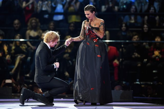 Co-host musician Ed Sheeran kneels to his co-host actress Ruby Rose appear on stage during the MTV EMA's 2015 at the Mediolanum Forum on October 25, 2015 in Milan, Italy. (Photo by Brian Rasic/Getty Images for MTV)