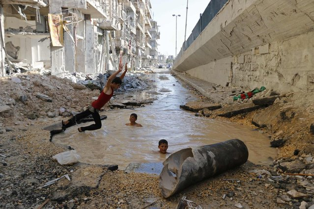 A youth dives into a crater filled with water in Aleppo's al-Shaar district, in this July 10, 2014 file photo. (Photo by Hosam Katan/Reuters)