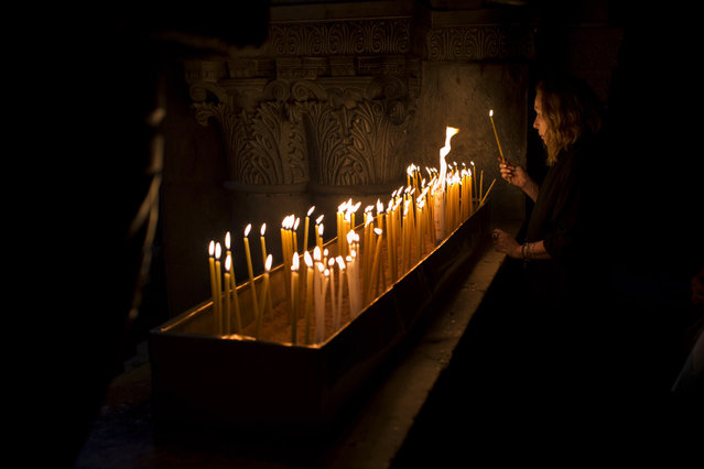 A Christian Catholic pilgrim lights a candle inside the Church of the Holy Sepulcher, traditionally believed to be the site of the crucifixion of Christ, in Jerusalem's Old City, Friday, March 29, 2013. Less than 2 percent of the population of Israel and the Palestinian territories is Christian, mostly split between Catholicism and Orthodox streams of Christianity. Christians in the West Bank wanting to attend services in Jerusalem must obtain permission from Israeli authorities. Israel's Tourism Ministry said it expects some 150,000 visitors in Israel during Easter week and the Jewish festival of Passover, which coincide this year. (Photo by Bernat Armangue/AP Photo)