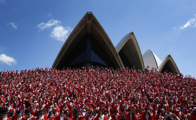 Thousands of runners in Father Christmas suits pose for a group photo after completing an annual Santa fun run from Darling Harbour to the Sydney Opera House, December 7, 2014. The annual event is held each year as a fundraiser to assist disadvantaged children with equipment and programs to help them live a fuller life. (Photo by Jason Reed/Reuters)