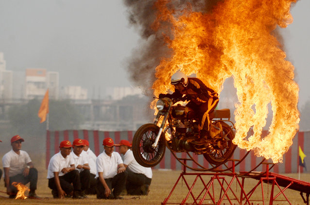"""An Indian army soldier member of the """"Tornadoes"""" motorcycle display team rides rings of fire during a combined display at an officer training academy in Chennai on March 9, 2018. (Photo by Arun Sankar/AFP Photo)"""