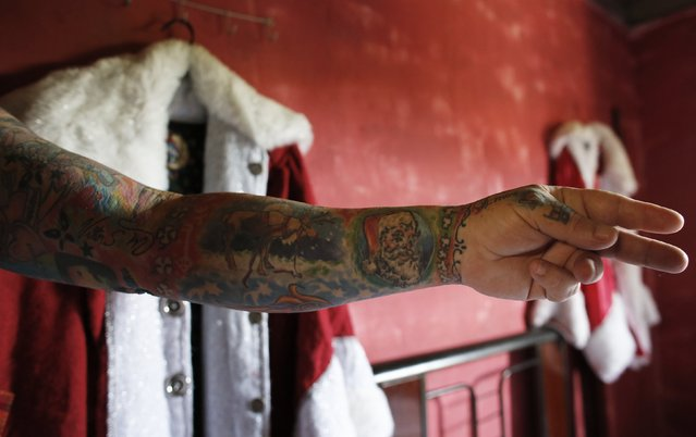 Vitor Martins displays one of his Christmas tattoos, in front of his Santa outfit inside his house, before a performance with children in Sao Caetano do Sul's town square, near Sao Paulo, December 7, 2014. (Photo by Nacho Doce/Reuters)