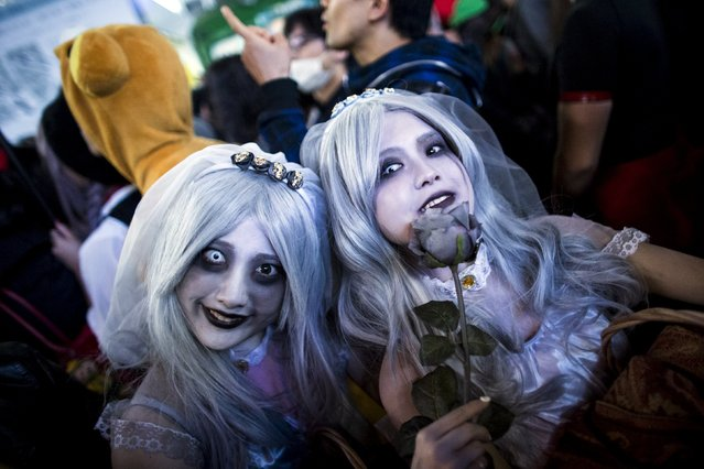 Revellers in costumes pose for pictures during Halloween celebrations in the Shibuya district in Tokyo, Japan October 31, 2015. (Photo by Thomas Peter/Reuters)