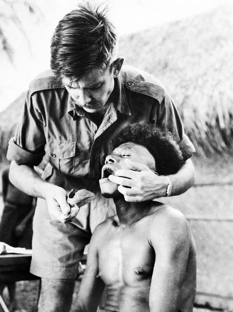 David Cameron, dentist with the Australian health survey party, takes a wax impression of a Trobriand islander's teeth in Papua New Guinea on March 1, 1948. The Australians spent seven months checking the health and diet of natives in five areas of Papua New Guinea. (Photo by AP Photo)