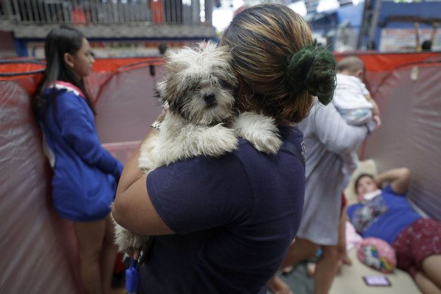A resident carries her dog inside an evacuation center as rains from a typhoon locally known as Goni start to pour in Manila, Philippines on Sunday, November 1, 2020. A super typhoon slammed into the eastern Philippines with ferocious winds early Sunday and about a million people have been evacuated in its projected path, including in the capital where the main international airport was ordered closed. (Photo by Aaron Favila/AP Photo)