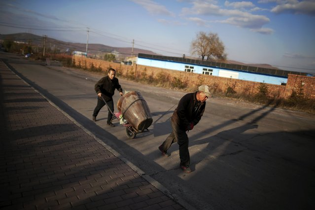 Miners carry their supplies for upcoming winter, towards a coal mine from the state-owned Longmay Group, on the outskirts of Jixi, in Heilongjiang province, China, October 24, 2015. (Photo by Jason Lee/Reuters)