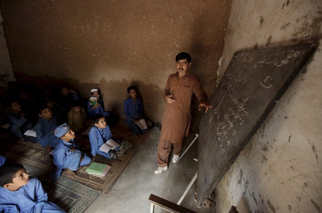 A man teaches students at a school in Kababiyan refugee camp in Peshawar, Pakistan, October 6, 2015. Aid programmes for some of the 2.5 million Afghan refugees in Pakistan are being slashed amid the worst funding shortfall for a generation, as the European and Syrian migrant crisis uses up cash and dominates headlines, United Nations officials said. (Photo by Faisal Mahmood/Reuters)