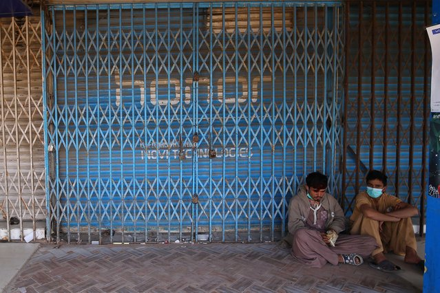 People sit at a closed market that was sealed during smart lockdown after new cases of COVID-19 were reported in Karachi, Pakistan, 02 November 2020. Countries around the world are taking increased measures to stem the widespread of the SARS-CoV-2coronavirus which causes the Covid-19 disease. (Photo by Shahzaib Akber/EPA/EFE)