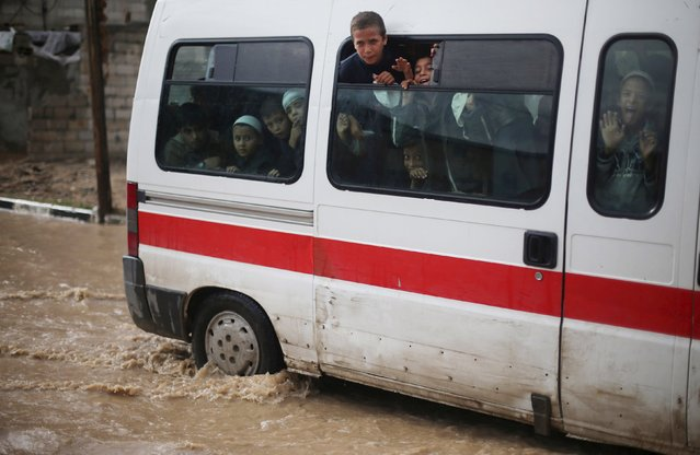 Palestinian students look out from a bus as they drive pass a street flooded by rain water in Khan Younis in the southern Gaza Strip, November 9, 2015. (Photo by Ibraheem Abu Mustafa/Reuters)