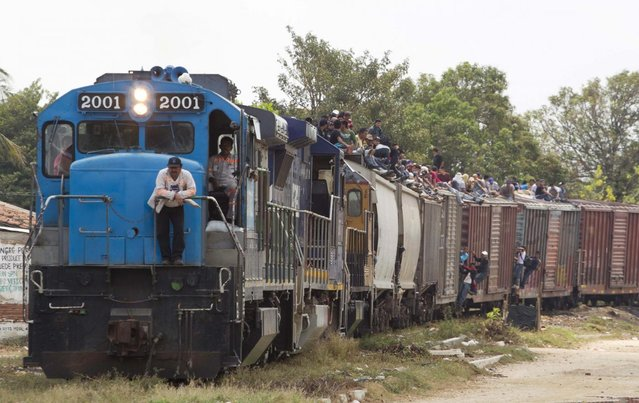 Migrants ride on top of a northern bound train toward the US-Mexico border in Ixtepec, southern Mexico, Monday, April 29, 2013. Migrants crossing Mexico to get to the U.S. have increasingly become targets of criminal gangs who kidnap them to obtain ransom money. (Photo by Eduardo Verdugo/AP Photo)