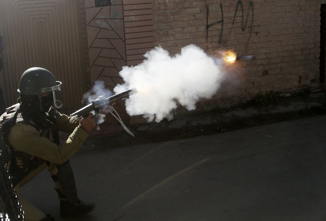 An Indian policeman fires tear smoke shell on Kashmiri protesters in Srinagar, India, Thursday, April 12, 2018. Indian forces used tear gas and pellet guns to disperse stone-throwing youth who were protesting against killing of three civilians Wednesday. (Photo by Mukhtar Khan/AP Photo)