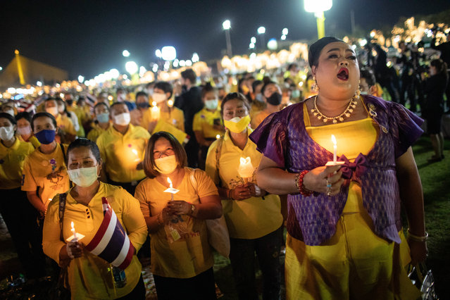 Thai royalist supporters hold candles at Sanam Luang in front of the Grand Palace during a ceremony to mark the birthday of the late Thai King Bhumibol Adulyadej (Rama 9) in Bangkok, Thailand on December 05, 2020. Thai King Maha Vajiralongkorn (Rama 9), was present during the ceremony. (Photo by Guillaume Payen/Anadolu Agency via Getty Images)