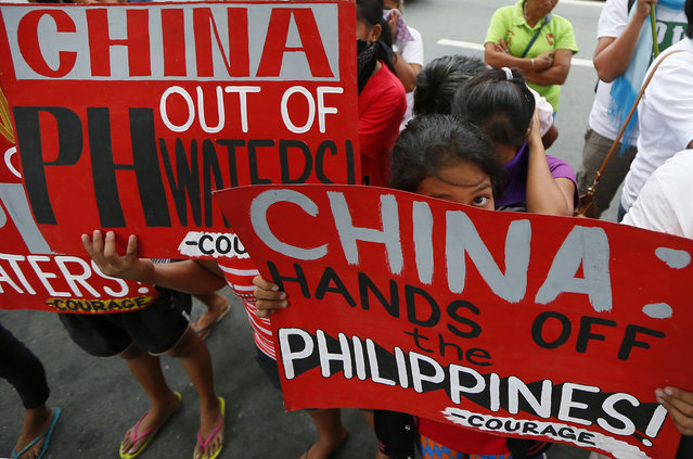 Protesters display placards during a rally at the Chinese consulate in the financial district of Makati city, east of Manila, Philippines Thursday, November 12, 2015, to protest China's land reclamation in the disputed Spratly island group in the South China Sea. The protesters are opposing the visit of Chinese President Xi Jinping attending the Nov. 18-19 APEC (Asia-Pacific Economic Cooperation) leaders summit. (Photo by Bullit Marquez/AP Photo)