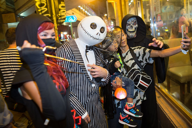 People in costume take photos during a Halloween event on October 31, 2015 in Lan Kwai Fong, Central District, Hong Kong. Halloween, a named taken from 'All Hallows' Even' falls on the day before All Saints' Day on November 1, a holiday when Christians remember their deceased loved ones. (Photo by Jerome Favre/Getty Images)