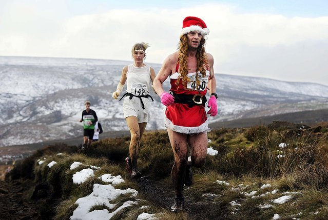 Costumed runners cross the Pennine hills near Haworth in northern England in the annual Auld Lang Syne 9.6-kilometer race, which includes a costume contest and free beer for all finishers, on December 31, 2014. (Photo by John Giles/PA Wire)