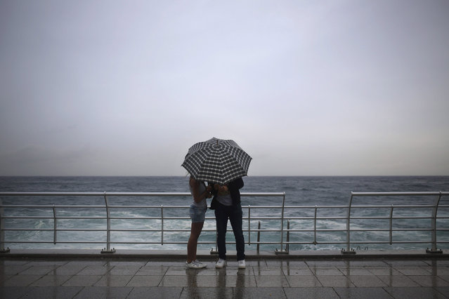 A Lebanese couple stand under an umbrella in rainy weather at the Corniche or waterfront promenade, in Beirut, Lebanon, Sunday, October 25, 2015. (Photo by Hassan Ammar/AP Photo)