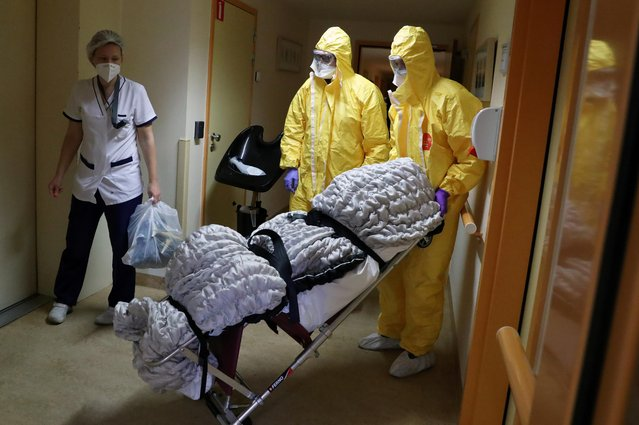 Mortuary employees transport the body of a person in an elderly residence following the coronavirus disease (COVID-19) outbreak in Brussels, Belgium on April 14, 2020. (Photo by Yves Herman/Reuters)